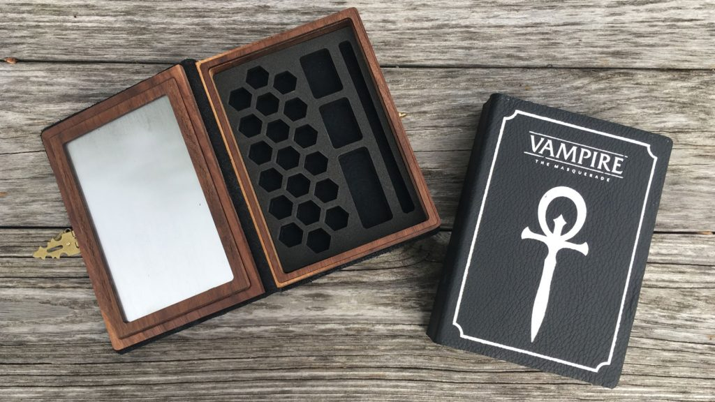Vampire the Masquerade edition Spellbooks shown open with foam insert and closed on a wood background