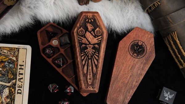 2 Mini Dice Sarcophagi, one partially open with a set of miniature dice and one closed with bottom facing up, next to tarot card, spellbook and D6