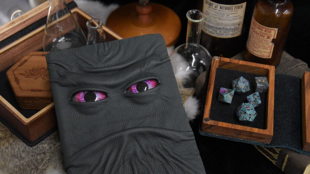 Spellbook gaming box with a monster face with gemstone dice and potion bottles
