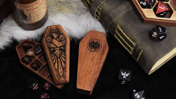 2 Mini Dice Sarcophagi, one open with Nightmare Black Mini Pebble Dice, one close with bottom facing up, next to a Hex Chest Remastered