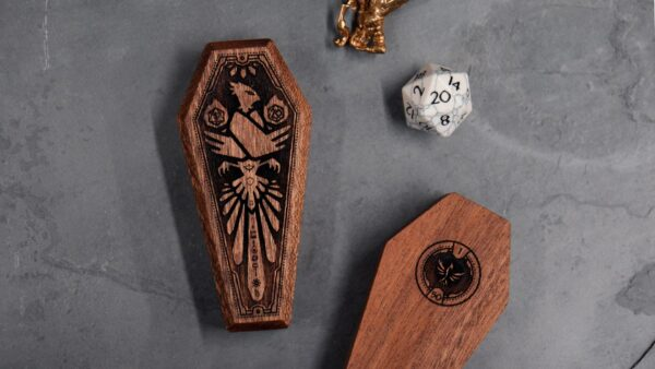2 closed Mini Dice Sarcophagi, showing top and bottom engraving, next to D20 and miniature figurine